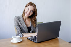 Cute young female adult working on laptop computer at desk next to coffee cup stock images