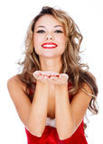 Cute young female in red dress blowing a kiss at you. Against white background Stock Images