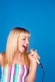 Cute young female singing song, isolated over blue Stock Photography