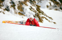 Cute young female skier after falling down stock images