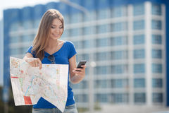 Cute young female traveler with a map of the city Stock Photo