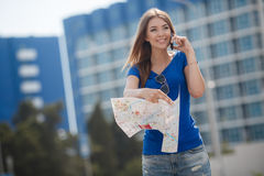 Cute young female traveler with a map of the city Royalty Free Stock Photography
