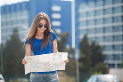Cute young female traveler with a map of the city Royalty Free Stock Photos