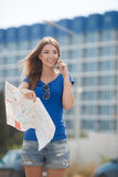 Cute young female traveler with a map of the city Royalty Free Stock Photo