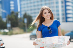 Cute young female traveler with a map of the city Royalty Free Stock Image
