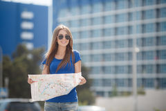 Cute young female traveler with a map of the city Stock Photos