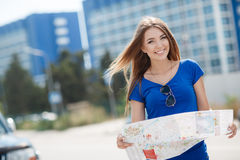Cute young female traveler with a map of the city Stock Images