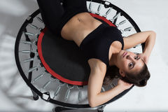 Cute young fitness-girl on rebounder Stock Photography