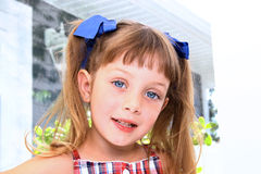Cute young girl. Portrait of cute young girl with ribbons in hair indoors Royalty Free Stock Photo
