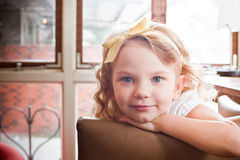 Cute young girl. Portrait of cut young preschool girl with blond hair relaxing on sofa or couch at home Royalty Free Stock Photo