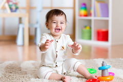 Cute young girl baby playing home with colorful toys Royalty Free Stock Image
