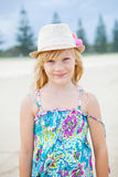 Cute young girl at beach. Portrait of cute young girl with summer dress and stylish hat at the beach Stock Photography