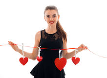 Cute young girl in a black dress smiles and keeps hands Red Ribbon with hearts. Isolated on white background Stock Images