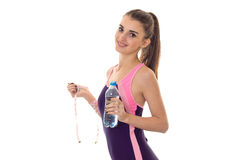Cute young girl in body looks at the camera smiling and holding a water bottle. Isolated on white background Stock Photos