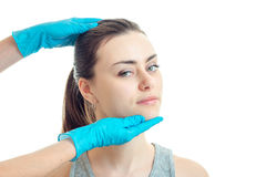 Cute young girl came to the doctor which wearing gloves checks her face close-up. Isolated on white background Stock Photography
