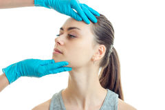 Cute young girl came to the plastic surgeon who examines her face in blue gloves close-up Royalty Free Stock Photos