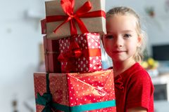 Cute young girl carrying stack of christmas presents, smiling and looking at camera. Happy kid at christmas. Cute young girl carrying stack of christmas stock image