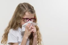 Cute young girl child in glasses sneezing in a tissue blowing stock image