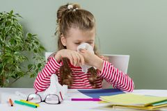 Cute  young girl child in glasses sneezing in a tissue blowing. His runny nose Stock Photo