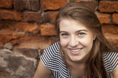 Cute young girl close-up portrait near a brick wall. Happiness Stock Photography