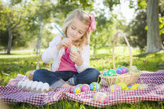 Cute Young Girl Coloring Her Easter Eggs with Paint Brush. Cute Young Girl Happily Coloring Her Easter Eggs with Paint Brush in the Park Stock Image