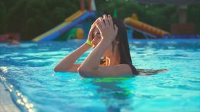 Cute and young girl dives into the pool in order to cool off on a hot day stock footage