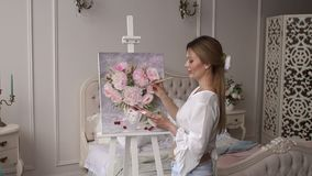 A young girl draws on canvas peony flowers at home in the bedroom. Cute young girl draws on canvas peony flowers at home in the bedroom in a modern interior, in stock video footage