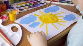 Cute young girl draws yellow sun and blue clouds. Painting concept stock footage