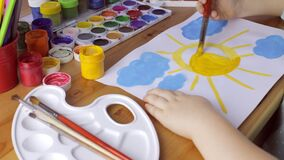 Cute young girl draws yellow sun on white paper stock video