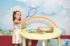 A cute young girl in a dress makes soap bubbles in the children`s room. A cute young girl in a dress makes soap bubbles in the children`s room stock photography