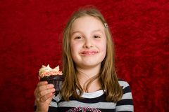 Cute young girl eating a cupcake Stock Images