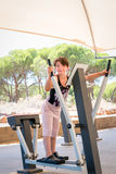 Cute young girl exercising arms and chest on cross trainer gym machine outdoors. Royalty Free Stock Photography