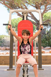 Cute young girl exercising upper body on gym machine outdoors. Royalty Free Stock Image