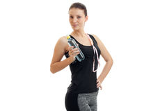 Cute young girl in fitness black t-shirt looks away and keeps the shoulder strap and a bottle of water in hand Stock Photography