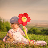 Cute young girl with flower in hand hugging a rabbit - Square composition Stock Image