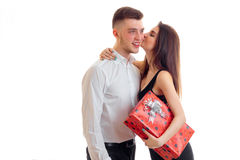 Cute young girl with a gift in hand kisses the guy`s cheek Stock Photos