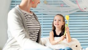 Cute young girl giving her mom a flower. Family celebration concept. Happy Mother`s Day or Birthday Background. royalty free stock photos