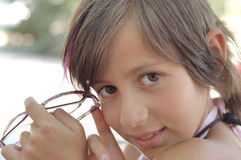 Cute young girl with glasses. Portrait of cute young girl with brunette hair holding glasses or spectacles Royalty Free Stock Photography