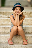 Cute young girl with hat sitting on stairs in park Royalty Free Stock Image