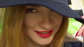 Cute young girl in hat with wide brim. And with red lips looking at the camera and smiling outdoors royalty free stock image