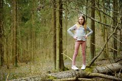 Cute young girl having fun during forest hike on beautiful early spring day. Active family leisure with kids. Family fun royalty free stock photos