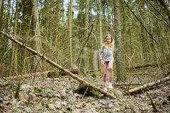 Cute young girl having fun during forest hike on beautiful early spring day. Active family leisure with kids. Family fun stock photography