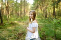 Cute young girl having fun during forest hike on beautiful summer day. Active family leisure stock photos