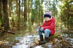 Cute young girl having fun during forest hike on beautiful winter day. Active family leisure with kids. Family fun royalty free stock photo