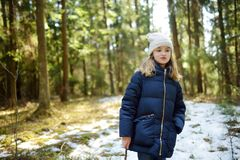 Cute young girl having fun during forest hike on beautiful winter day. Active family leisure with kids. Family fun royalty free stock photography