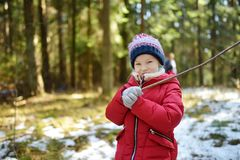 Cute young girl having fun during forest hike on beautiful winter day. Active family leisure with kids. Family fun royalty free stock photos
