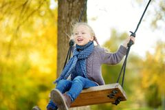 Cute young girl having fun on a swing in sunny autumn park. Family weekend in a city royalty free stock photography