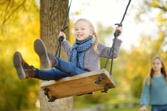 Cute young girl having fun on a swing in sunny autumn park. Family weekend in a city royalty free stock images