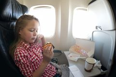 Cute young girl having meal in the airplane while flying. Royalty Free Stock Photos