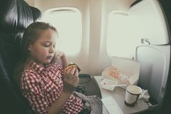 Cute young girl having a meal in the airplane while flying Stock Images